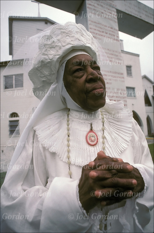 Mother Essie McDonald in her 80s praying in front of Mt Zion Church which she founded in Crescent City FL