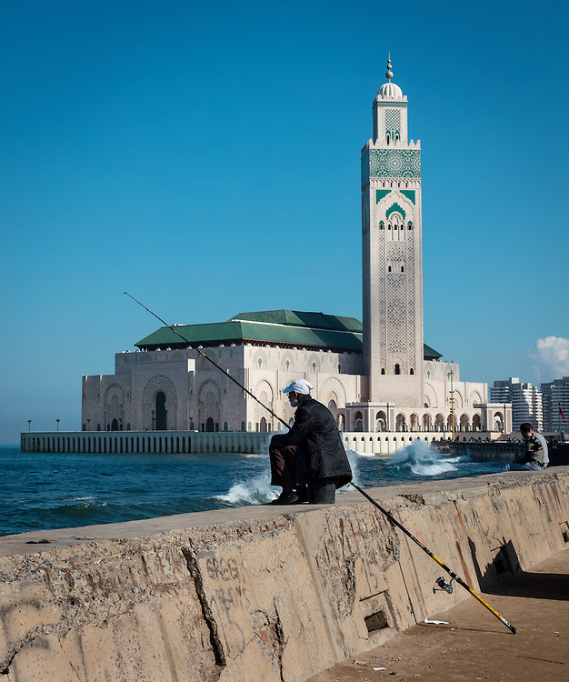 A fisherman sits on the break wall next to the famous Hassan II Mosque in Casablanca, Morocco.
