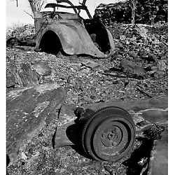 An old car left in ruins after a small forest fire.