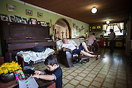Caracciolo Viloria, abuelo paterno de Yuliana descansa en su casa mientras sus nietos hacen labores escolares. Gracias a FundaHigado, Yuliana recibió un trasplante de higado que le permite disfrutar de la vida. Punto Fijo, Venezuela 26 y 27 Oct. 2012. (Foto/ivan gonzalez)