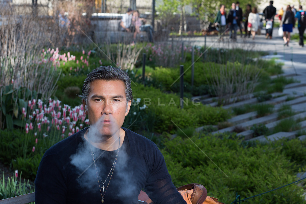 Asian American man blowing smoke out of his nose while seated at the High Line in New York City