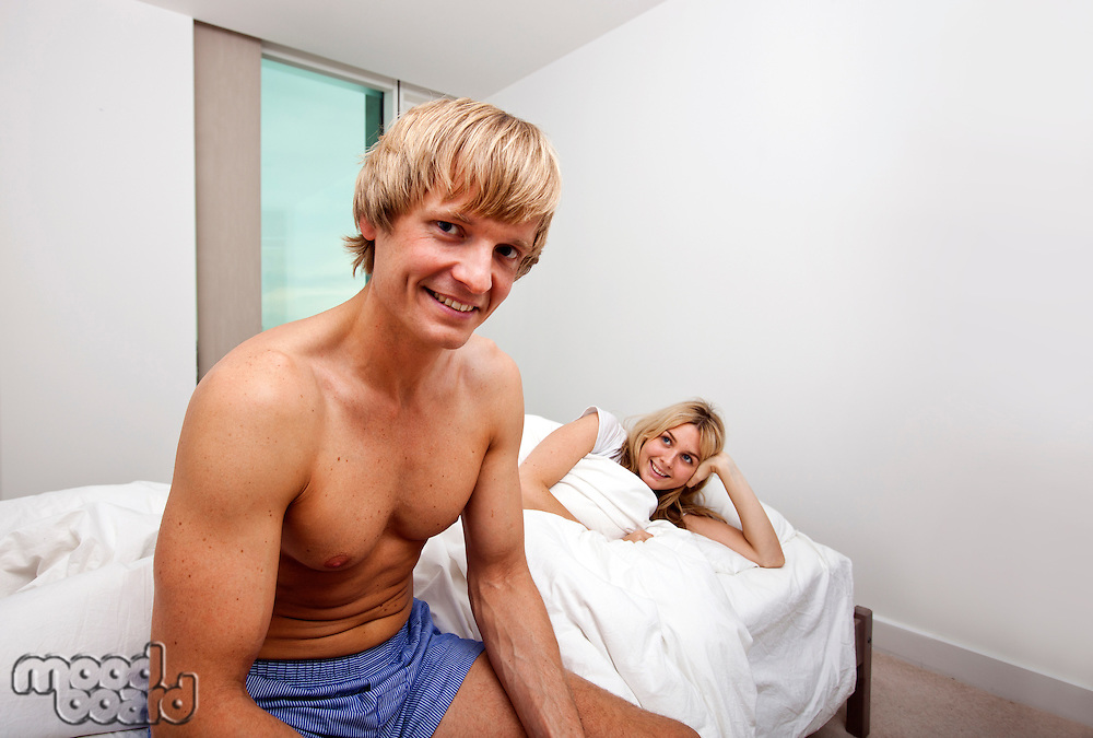 Portrait of man in underwear sitting on bed with woman looking at him