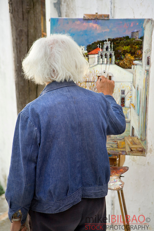 Painter and canvas on the street. Aperanthos. Naxos island. Cyclades islands, Aegean Sea, Greece, Europe.