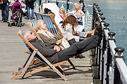 © Licensed to London News Pictures. 18/04/2014. Brighton, UK. People relax in deck chairs on the pier.  People enjoy the  bank holiday sunshine at Brighton today 18th April 2014. Photo credit : Stephen Simpson/LNP