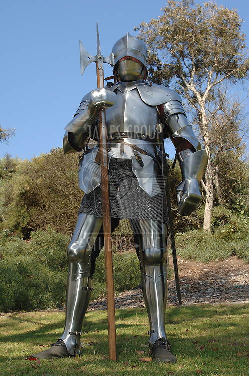 15th century English knight in full armour standing with battle axe shot from the front with a worm's eye view