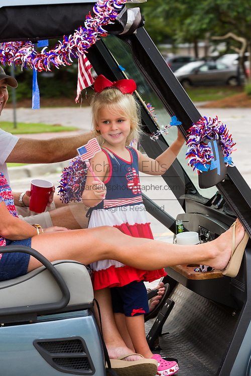 A young girl waves a flag from a golf cart decorated with bunting during the Daniel Island Independence Day parade July 3, 2015 in Charleston, South Carolina.