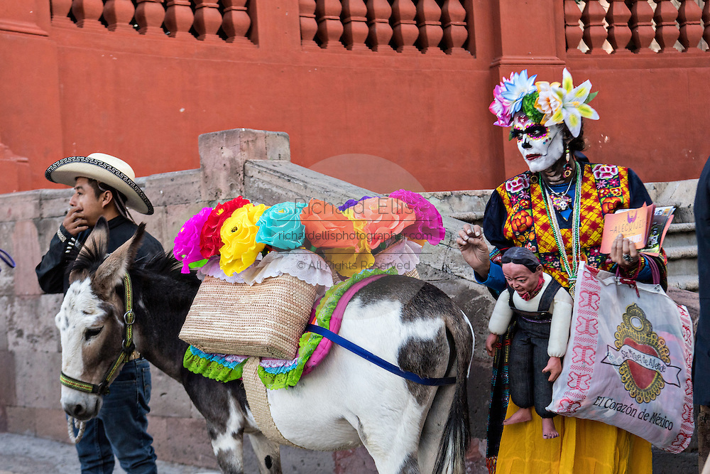 A woman dressed as La Calavera Catrina looks at a decorated donkey during the Day of the Dead festival October 28, 2016 in San Miguel de Allende, Guanajuato, Mexico. The week-long celebration is a time when Mexicans welcome the dead back to earth for a visit and celebrate life.