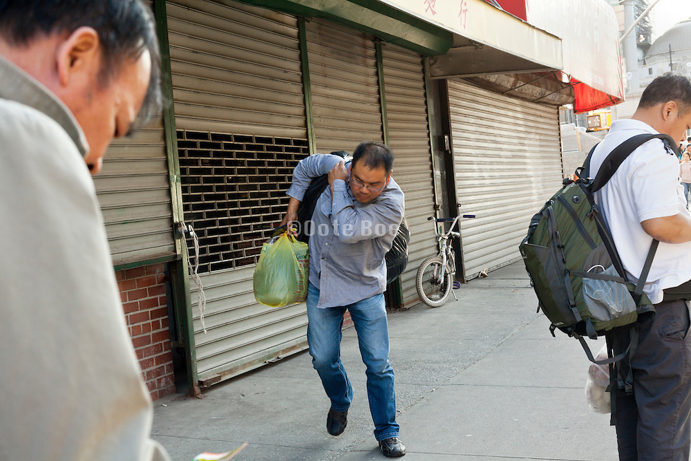 man walking with very heavy bag on the Lower Eastside in New York City