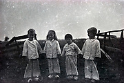 smiling happy children posing by the gate of a farmers field Netherlands 1950s