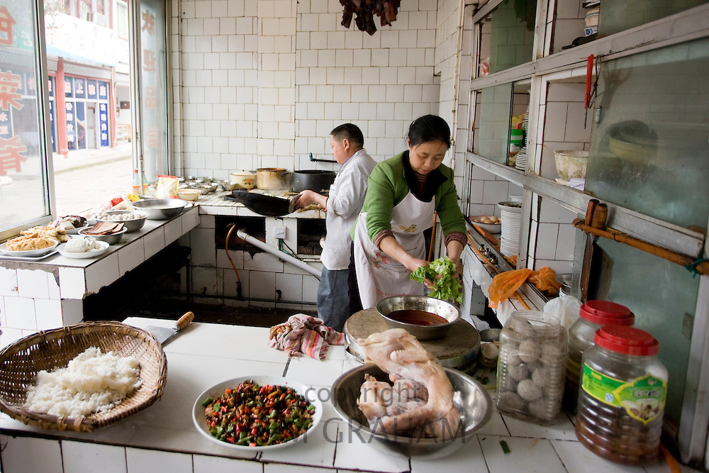 Chefs at work cooking in local street restaurant at Baoding in Dazu County, Chongqing, China