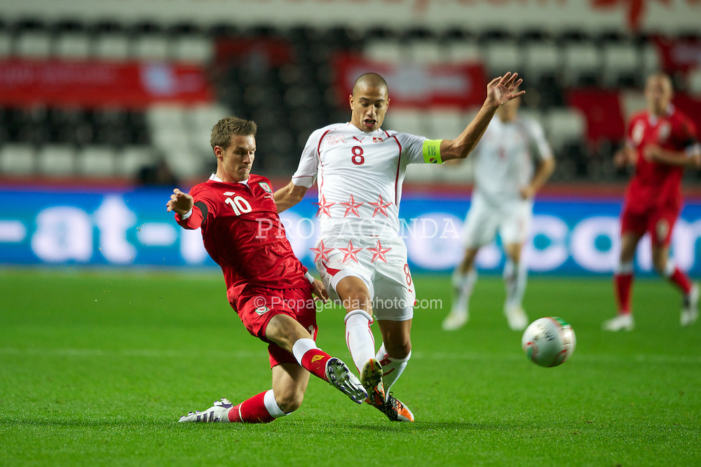 SWANSEA, WALES - Friday, October 7, 2011: Wales' Aaron Ramsey in action against Switzerland's captain Gokhan Inler during the UEFA Euro 2012 Qualifying Group G match at the Liberty Stadium. (Pic by Chris Brunskill/Propaganda)