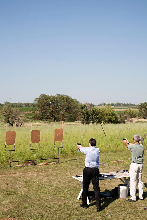 Republican presidential hopeful Tim Pawlenty (L) fires a gun at a shooting range with his brother Dan Pawlenty (R) during a campaign stop on Wednesday, July 20, 2011 in Madrid, IA.