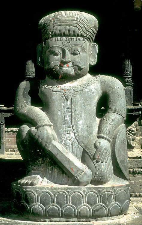 Bhaktapur, World Heritage city, statue of Shiva with trident; basalt; at the base of the Datatreya Temple, built by King Yaksha Malla, 1428.  Frontal view of the squatting figure, holding a club..