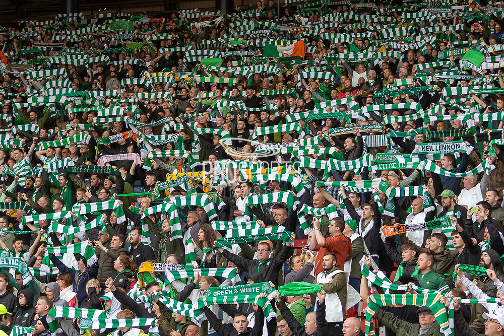 Celtic fans hold their scalfs aloft and sing as their team parades the Scottish Cup around Hampden Park, Glasgow, United Kingdom on 25 May 2019.