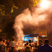 The smoke rises from a food sellers cooking as fans queue for food outside the Olympic Stadium after the Fluminense V Corinthians, Futebol Brasileirao League match at the Olympic Stadium, Corinthians won the match 2-1. Rio de Janeiro. Brazil. 15th September 2010. Photo Tim Clayton.