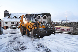 © Licensed to London News Pictures. 17/01/2018. Tebay, UK. A digger clears snow from the entance to the Westmoreland hotel after heavy overnight snow. Photo credit: John France/LNP