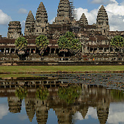 Angkor Wat (Khmer: អង្គរវត្ត) was first a Hindu, later a Buddhist, temple complex in Cambodia and the largest religious monument in the world. The temple was built by the Khmer King Suryavarman II in the early 12th century in Yaśodharapura (Khmer: យសោធរបុរៈ, present-day Angkor), the capital of the Khmer Empire, as his state temple and eventual mausoleum. Breaking from the Shaiva tradition of previous kings, Angkor Wat was instead dedicated to Vishnu. As the best-preserved temple at the site, it is the only one to have remained a significant religious center since its foundation. The temple is at the top of the high classical style of Khmer architecture. It has become a symbol of Cambodia, appearing on its national flag, and it is the country's prime attraction for visitors.<br /> <br /> Angkor Wat combines two basic plans of Khmer temple architecture: the temple-mountain and the later galleried temple, based on early Dravidian architecture, with key features such as the Jagati. It is designed to represent Mount Meru, home of the devas in Hindu mythology: within a moat and an outer wall 3.6 kilometres (2.2 mi) long are three rectangular galleries, each raised above the next. At the centre of the temple stands a quincunx of towers. Unlike most Angkorian temples, Angkor Wat is oriented to the west; scholars are divided as to the significance of this. The temple is admired for the grandeur and harmony of the architecture, its extensive bas-reliefs, and for the numerous devatas adorning its walls.<br /> <br /> The modern name, Angkor Wat, means &quot;Temple City&quot; or &quot;City of Temples&quot; in Khmer; Angkor, meaning &quot;city&quot; or &quot;capital city&quot;, is a vernacular form of the word nokor (នគរ), which comes from the Sanskrit word nagara (नगर). Wat is the Khmer word for &quot;temple grounds&quot; (Sanskrit: वाट vāṭa &quot;&quot;enclosure&quot;).