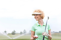 Happy middle-aged woman looking away while holding golf club and ball