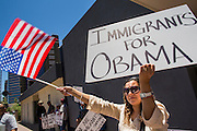 15 JUNE 2012 - PHOENIX, AZ:   AIDA LOPEZ walks along a sidewalk in Phoenix Friday carrying a sign thanking President Obama for his immigration announcement. President Barrack Obama announced Friday that fffective immediately, young people who were brought to the US through no fault of their own as children and who meet certain criteria will be eligible to receive deferred action for a period of 2 years and that period will be subject to renewal. The announcement of the new executive order means that up to 800,00 young undocumented immigrants will not be deported and can continue their education in the US. The move was seen by many in the immigrant community as the closest thing they would get to seeing the DREAM Act passed in the near future.     PHOTO BY JACK KURTZ