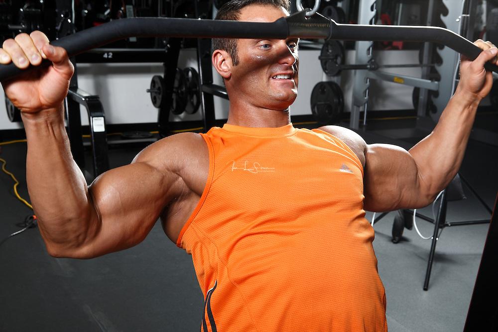 Bodybuilder Dan Decker working out, weightlifting in the gym.