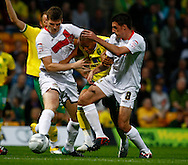 Gary MacKenzie and Darren Potter of MK Dons squeeze out Norwich's Simeon Jackson during the Carling Cup 2nd Round match at Carrow Road Stadium, Norwich, Norfolk...Picture by Paul Chesterton/Focus Images Ltd.  07904 640267.23/8/11