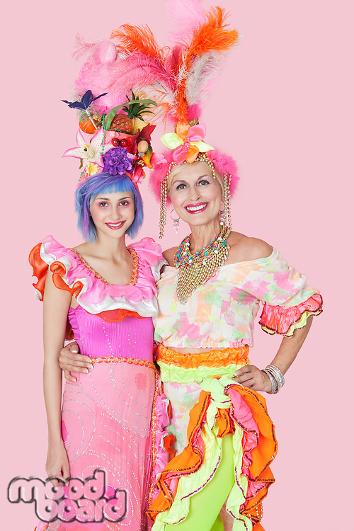 Portrait of happy young and senior women in Brazilian outfits over pink background