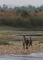 People walking over rocks to cross a river, Bardiya National Park, Nepal
