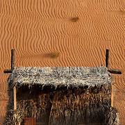 Oman, Wahiba Sands. January/24/2008...The sun sets on the Barasti-styled accomodations of Nomadic Desert camp.