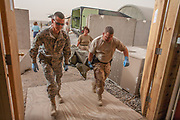 Transported by U.S. Army medevac helicopter, a multi-national team of doctors and nurses rush a battlefield casualty into Kandahar Airfield Hospital, Kandahar Province, Afghanistan.