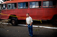 A bus driver lays dead in his seat after a unknown assailant got onto the bus and shot the driver in the head killing him instantly and sending the bus to crash into a tree in Premero Julio Zone 19 Guatemala City Guatemala, 13 January   2009.