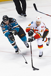 Feb 8, 2012; San Jose, CA, USA; Calgary Flames center Olli Jokinen (13) passes the puck in front of San Jose Sharks left wing Patrick Marleau (12) during the third period at HP Pavilion. Calgary defeated San Jose 4-3. Mandatory Credit: Jason O. Watson-US PRESSWIRE