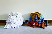 A pile of white laundry and a pile of colored laundry.