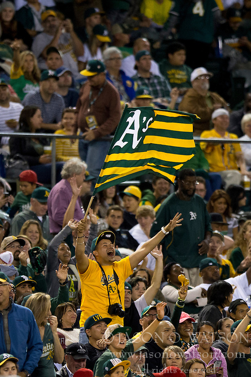 OAKLAND, CA - SEPTEMBER 23:  An Oakland Athletics fan waves a flag during the fifth inning against the Los Angeles Angels of Anaheim at O.co Coliseum on September 23, 2014 in Oakland, California. The Los Angeles Angels of Anaheim defeated the Oakland Athletics 2-0.  (Photo by Jason O. Watson/Getty Images) *** Local Caption ***
