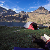 Backpacker reading at sunset. Upper Jean Lake. Wind River Wildernss Area, Wyoming.
