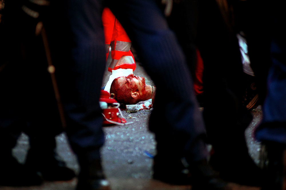 The body of 23 year-old protestor, Carlo Giuliani, is surrounded by Carabinere after being shot dead by a young police conscript during violent anti-globalization protests in the centre of Genoa. Banks, shops and cars were burnt and looted. The historic centre of the town was sealed off for the G8 Summit after 40 percent of the city's population left the city. 15,000 police and army personnel sealed off the city centre in anticipation of violent demonstrations.