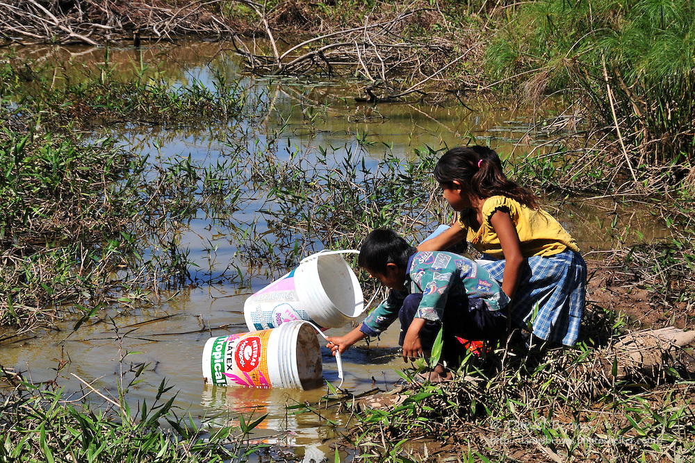 Yuracare children dip buckets of water from a swamp in Beni, Bolivia