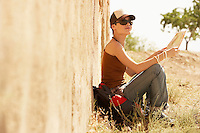 female hiker holding map sitting on ground by rustic house