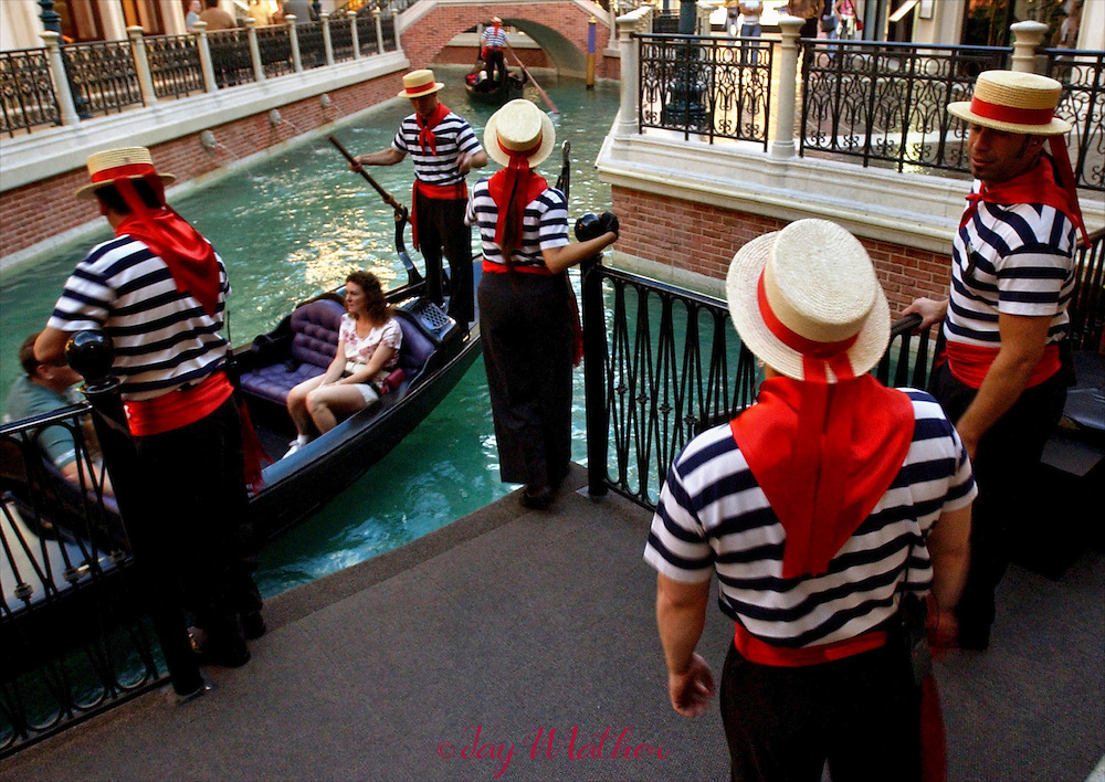 "Actors portray gondoliers while giving visitors rides on the Venetian Hotel and Casino ""canals, "" Tuesday, April 20, 2004.  The attraction is modeled after the Italian city built on water and in a city, Las Vegas,  built in a desert."