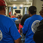 WALDORF, MD - AUG20: Union workers lean in to an overflowing conference room to hear to public comments about the proposed gas-fired power plant made to the Maryland Public Service Commission, August 20, 2015, at the Charles County Public Library, in Waldorf, Maryland. The plant would become the fifth plant in a 13-mile radius in southern Maryland and drew a standing room only crowd to comment on the record. (Photo by Evelyn Hockstein/For The Washington Post)