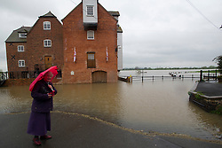 © London News Pictures. 01/05/2012. Tewkesbury, UK. An elderly woman with an umbrella looking at flood water which is approaching houses in Tewkesbury, Gloucestershire, England on May 1, 2012. The UK has had its wettest April in over a century, with some areas seeing three times their usual average rainfall, according to figures from the Met Office. Photo credit : Ben Cawthra /LNP