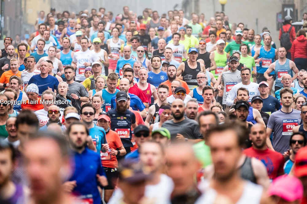 Runners make their way down the Royal Mile towards the Scottish Parliament Building at Holyrood during the Edinburgh Marathon 2018