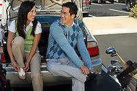 Couple Sitting on Rear Bumper of Car Putting on Golf Shoes