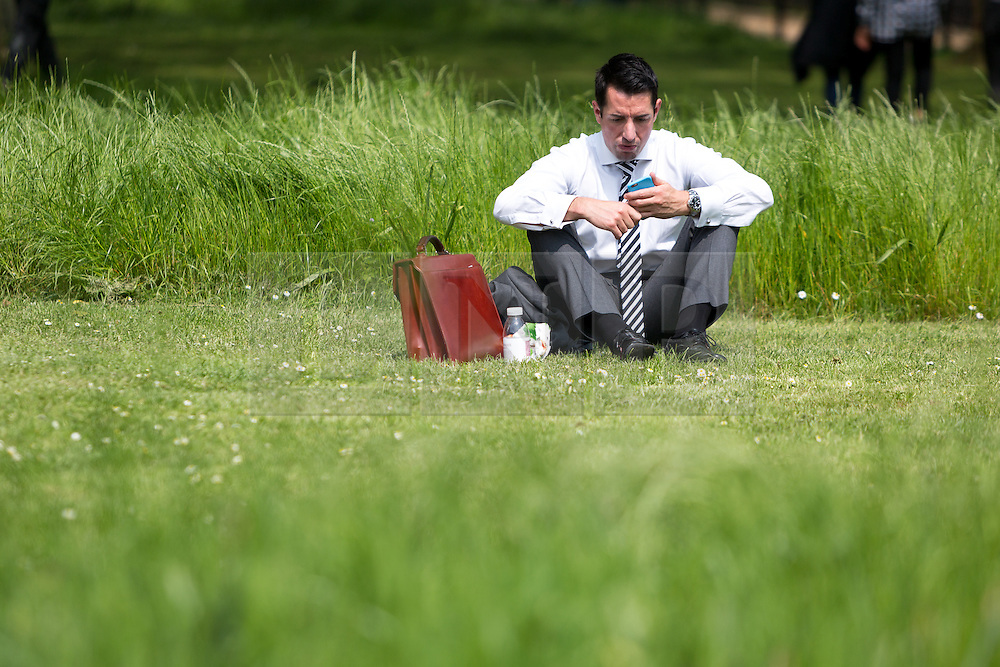 © Licensed to London News Pictures. 12/05/2016. LONDON, UK.  A businessman relaxes on the grass during warm sunny weather in St James's Park at lunchtime.  Photo credit: Vickie Flores/LNP