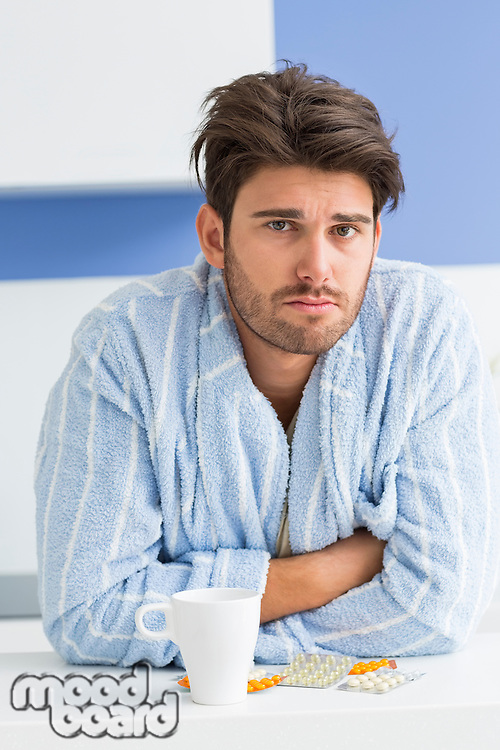 Portrait of ill man with coffee mug and medicine leaning on kitchen counter