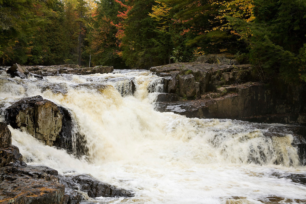 Waterfall in Phillilps Brook river with fall color trees in background.