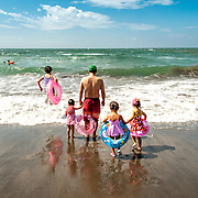 A family enters the water at Yuigahama Beach in Kamakura, Japan, about 45km south of Tokyo.