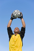 Goalkeeper catching soccer ball portrait