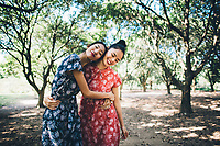 Two Asian women in matching dresses walk through a green garden in the countryside.