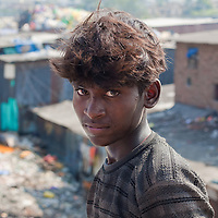 A young boy pauses from flying a kite in the Dharavi Slums of Mumbai.  Dharavi is the largest slums in the world and has a population of 600,000 to 1 million people.