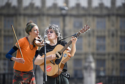 © Licensed to London News Pictures. 18/04/2019. London, UK. People perform music as campaigners from Extinction Rebellion occupy Parliament Square for a fourth day. Protesters are demanding urgent government action on climate change. Photo credit: Ben Cawthra/LNP